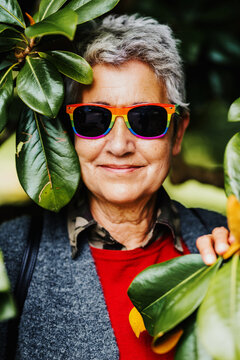 of older lady from the lgbt Vertical portrait of older lady from the lgbt community smiling with sunglasses among green plants. Lesbian granny. other sexualities concept