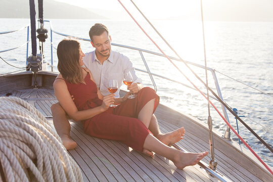 Couple in love drinking wine on yacht by sea. Happy travelers relaxing, traveling and enjoying summer vacation