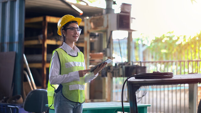 asian industrial Engineer manager woman wearing eyeglass and helmet  using digital tablet checking industry manufacturing large factory . female inspection worker
