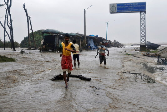 People run through a waterlogged road due to rising sea level ahead of Cyclone Yaas at Digha