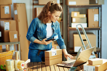 Obraz happy female in jeans using phone applications in warehouse - fototapety do salonu