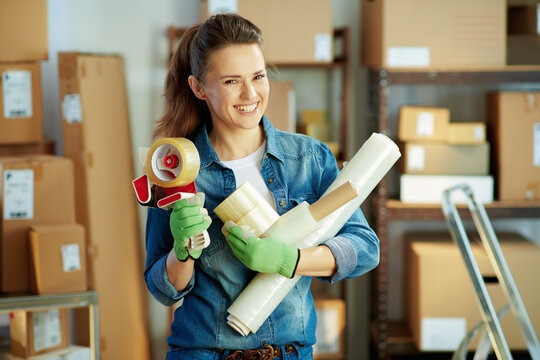 Portrait of happy young woman in jeans in warehouse