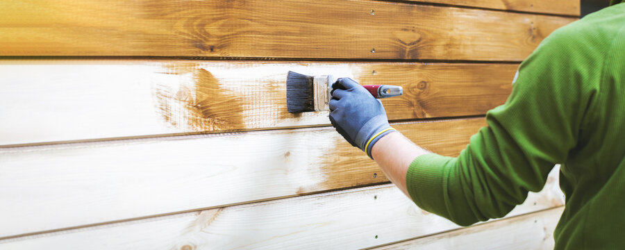 man painting wood house exterior siding with brown protective paint. banner copy space