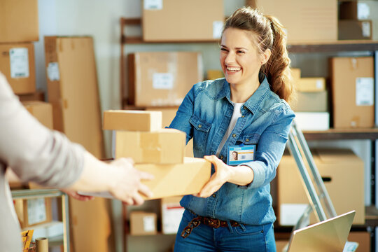 happy young female in jeans in warehouse giving parcel