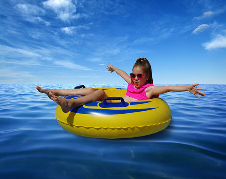 Little girl on inflatable ring in blue sea water