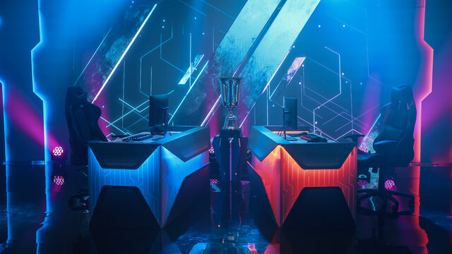Two Person Empty Computer Gaming eSports Championship Arena with Winner Trophy Standing on a Stage. Stylish Online Live Streaming Tournament with Big Screens Showing Graphics and Neon Stage