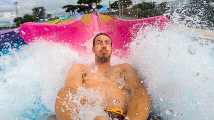 Fototapeta Selfie 40s man sliding a water slide very fast, splashing into the pool with water drops on the face. Having fun at a Water Amusement Park on summer vacation. obraz