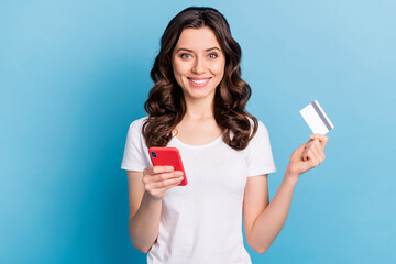 Photo of pretty cute young lady dressed white outfit holding modern gadget bank card isolated blue color background - fototapety na wymiar