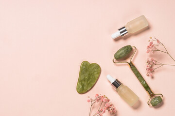 Obraz Jade roller and gua sha stone massager at pastel background. Anti-aging therapy. Top view. - fototapety do salonu