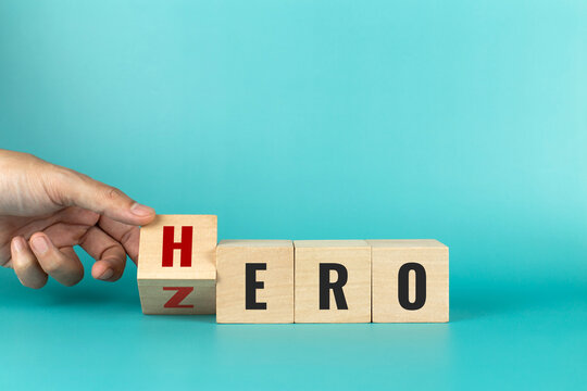Hand flip wooden cube with the word ZERO to HERO on blue background. Change for the better. Concept of personal development