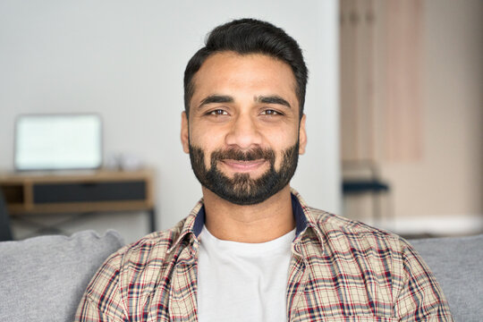 Headshot portrait of attractive confident indian Hispanic man looking at camera sitting on coach at modern living room. Latin businessman posing in casual stylish look at home office.