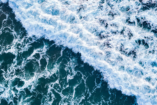 Open sea from aerial top view. Blue water frothy indonesia ocean surface with big wave