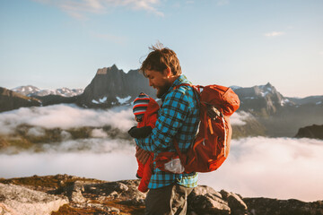 Obraz Father hiking with baby in mountains family vacations outdoor in Norway adventure healthy lifestyle man with child infant enjoying view weekend getaway backpacking activity - fototapety do salonu