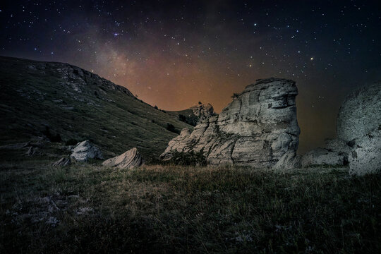 Milky Way over rocks at the top of Mount Demerdzhi in Crimea in Russia. Starry summer night. The top is overgrown with grass