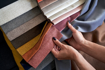 Choosing upholstery fabric color and texture from various colorful samples in a store. Female customer hands touching textile.