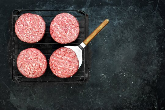 Grill Barbecue Grate with Raw Beef Hamburger Patties. Ground Beef Patties for Grilling and Roasting. Raw Minced Steak Burgers from Beef Meat on Black Background. Burger Cutlets On Paper And Grate.