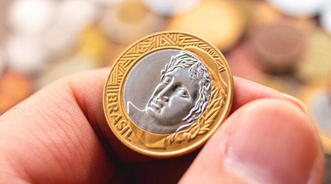 Dinheiro, Real, Brasil. Um homem segurando uma moeda de 1 Real em fotografia macro. Conceito de Finanças, economia brasileira e renda.