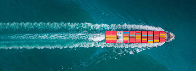 Obraz Aerial top view of cargo ship with contrail in the ocean sea ship carrying container and running for export from container international port to custom ocean concept freight shipping by ship service - fototapety do salonu