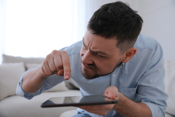 Emotional man with tablet at home. Online hate concept - fototapety na wymiar