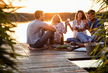 Obraz Group of friends having fun on picnic near a lake, sitting on pier eating and drinking wine. - fototapety do salonu