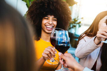 Obraz Happy african american woman drinking red wine at bar restaurant - Multiracial friends having fun celebrating at dinner time toasting drinks - Friendship concept - fototapety do salonu