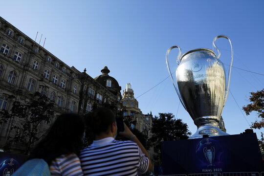 People take pictures of an inflatable model of the Champions League cup in Porto's central Aliados square as thousands of English fans make their way to Portugal's northern city for the League's final match and hotels and bars hope for a boost after the to