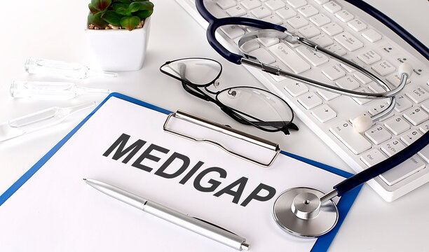 MEDIGAP text on white paper on white background. stethoscope ,glasses and keyboard