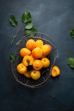 Overhead view of ripe apricots on dark surface