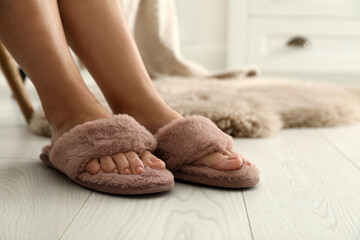 Woman in fluffy slippers at home, closeup