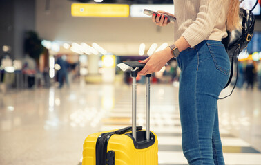 Fototapeta Young woman holding phone and yellow suitcase luggage with passport and plane ticket at airport obraz