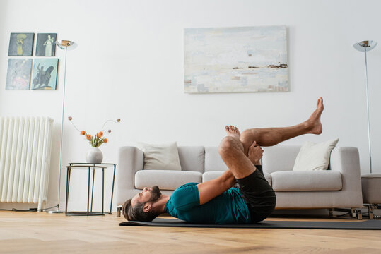 side view of man practicing pigeon pose on yoga mat at home