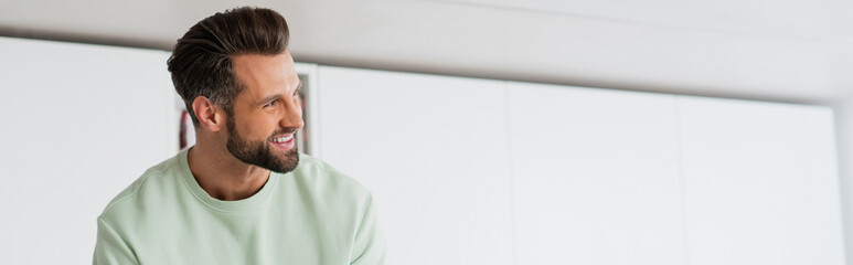 adult man smiling while looking away at home, banner