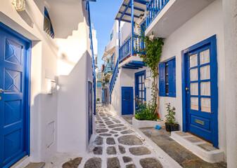Beautiful traditional narrow alleyways of Greek island towns. White houses, flower pots, blue balconies and doors. Mykonos, Greece