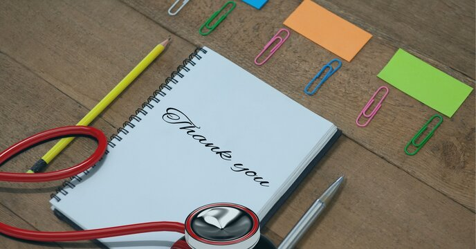 Composition of notebook with thank you note, with stethoscope and stationery on wooden desk