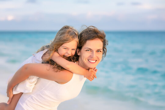 Portrait of happy mother and little daughter on ocean beach on Maldives at summer vacation. Family on the beach concept.