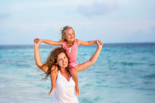 Happy mother and little daughter having fun on beach on Maldives at summer vacation. Family on the beach concept.