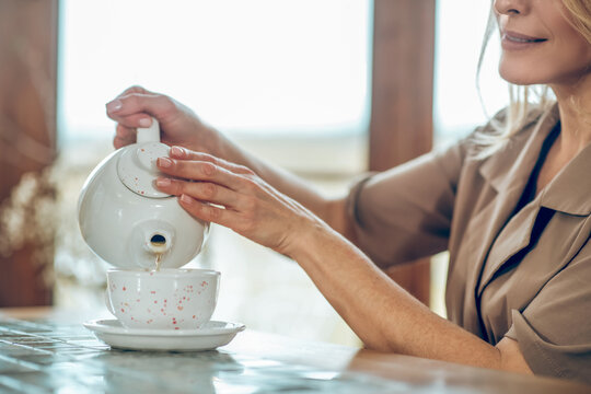 A pretty woman pouring tea from the tea pot to the cup