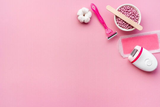 Pink epilator with wax strips and razor for removal of unwanted hair. Flat lay