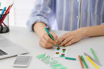 Fototapeta Woman coloring bookmark at table obraz