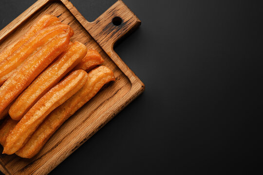 Board with tasty churros on dark background