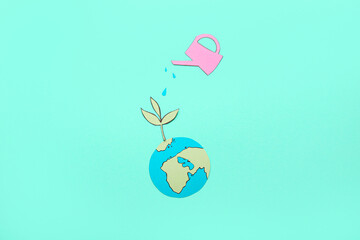 Fototapeta Paper planet Earth with green plant and watering can on color background. Ecology concept obraz