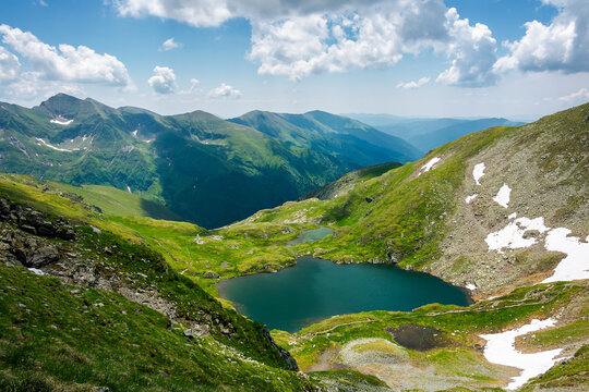 capra lake of fagaras mountains. wonderful summer nature scenery on a sunny day. popular travel destination of romania. snow and grass on the slopes. fluffy clouds on the sky