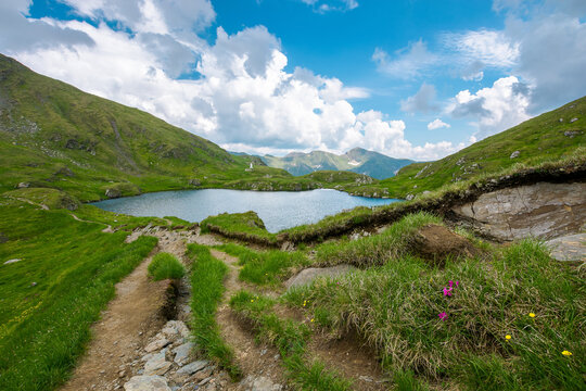 landscape with lake in mountains. wonderful summer nature scenery on a cloudy day. popular travel destination of fagaras ridge, romania. grass and stones on the slopes. dramatic clouds on the sky