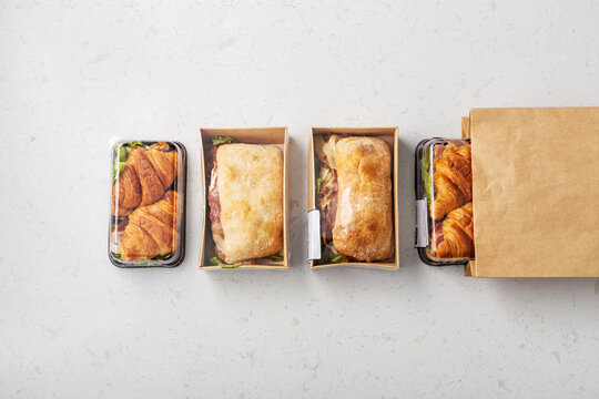 Sandwich in takeaway or delivery food box and paper bag