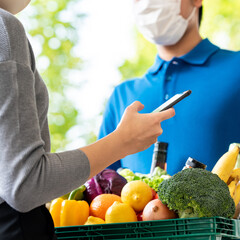 Fototapeta Deliveryman wearing face mask delivering groceries to woman customer that ordered online at home, food delivery service in the times of pandemic cancept obraz