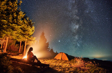 Young woman hiker sitting on bench near bonfire under magical sky with stars and Milky way. Beautiful view of night starry sky over grassy hill with camp tents and girl traveler near campfire. - fototapety na wymiar