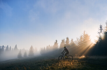 Side view of young man in cycling suit riding bicycle illuminated by morning sunlight. Male bicyclist cycling on grassy hill in the morning. Concept of sport, bicycling and active leisure. - fototapety na wymiar