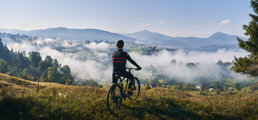 Obraz Man riding bicycle on grassy hill and looking at beautiful misty mountains. Male bicyclist enjoying panoramic view of majestic mountains during bicycle ride. Concept of sport, bicycling and nature. - fototapety do salonu