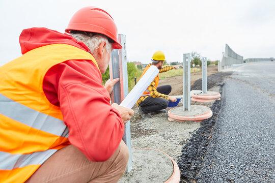 Bauarbeiter bei Kontrolle der Leitplanken Konstruktion