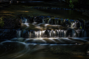 Cascading waterfall cascades in Estonia in green light at summertime Wall mural